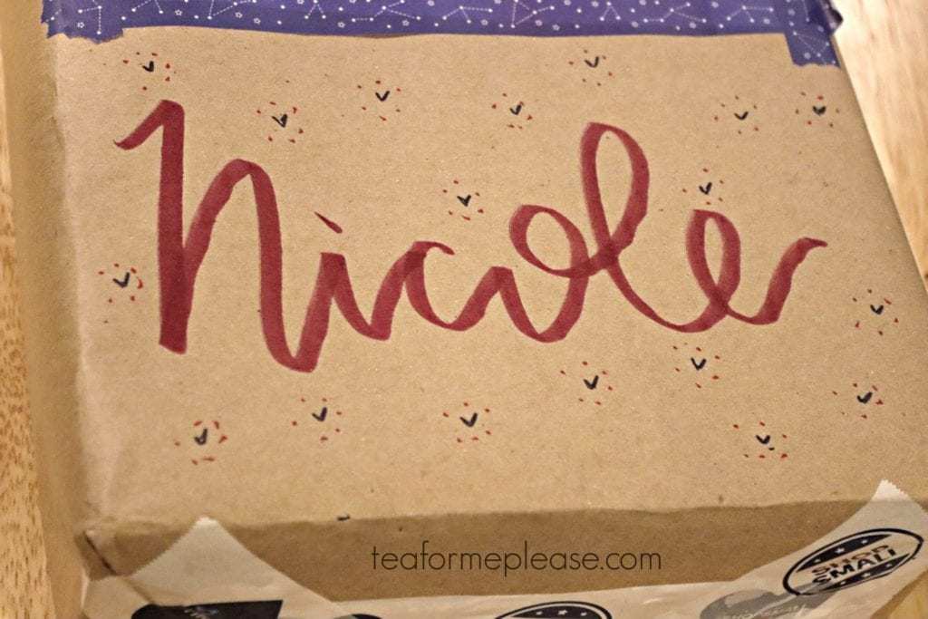 Brown paper wrapped box with Nicole written on it