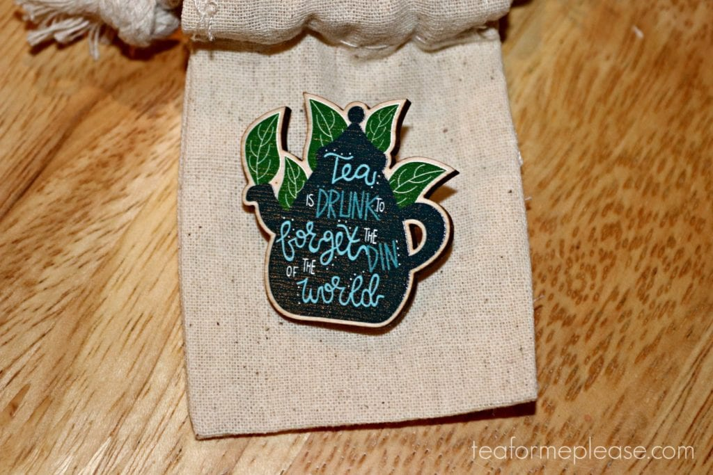 "Blue teapot surrounded by tea leaves and emblazoned with ""Tea is drunk to forget the din of the world"""
